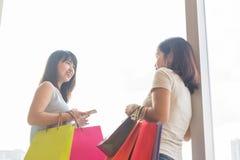 Le kvinnor som bär shoppingpåsar och samtal arkivbild