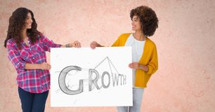 Le kvinnor som rymmer affischtavlan med tillväxttext mot persikabakgrund Arkivfoton