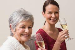 Le kvinnor som rymmer exponeringsglas av champagne Arkivfoto