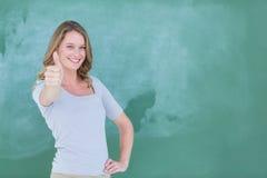 Le läraren den stående up tummar framme av svart tavla Fotografering för Bildbyråer
