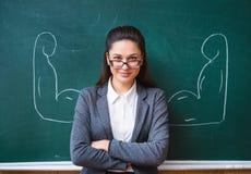 Le läraren i exponeringsglasen nära brädet arkivfoton