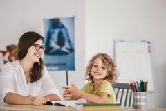 Le läraren och den lyckliga ungen som gör läxa efter grupper royaltyfria bilder