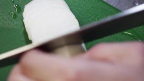 Le légume blanc est coupé en anneaux avec le couteau pointu sur la table de cuisine verte banque de vidéos