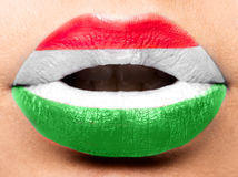 Le labbra femminili si chiudono su con una bandiera dell'immagine dell'Ungheria Nero, rosso, giallo Fotografia Stock