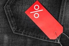 Le label rouge avec des pour cent se connectent le denim Photographie stock