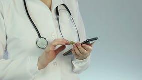 Le laboratoire médical femelle de visionnement des employés résulte utilisant le smartphone, progrès technique banque de vidéos