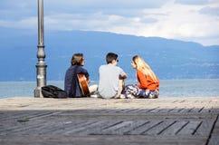 Le LAC de POLICIER, ITALIE 20 peut groupe de 2017 amis jouant la guitare dans le pilier de coucher du soleil au crépuscule Photos stock