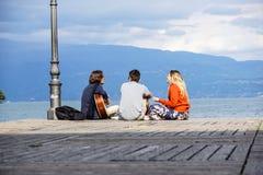 Le LAC de POLICIER, ITALIE 20 peut groupe de 2017 amis jouant la guitare dans le pilier de coucher du soleil au crépuscule Images libres de droits
