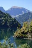 Le lac est entouré par des montagnes et des forêts Photo libre de droits