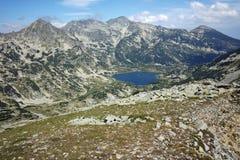 Le lac et le Polezhan Popovo font une pointe, crête de Dzhano de forme de vue, montagne de Pirin Images libres de droits