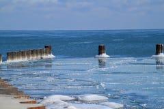 Le lac Michigan congelé avec les roches glaciales et les poteaux en bois Images stock
