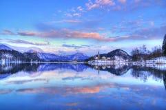 Le lac a saigné, l'église de l'acceptation de Vierge Marie, île saignée, Slovénie - coucher du soleil dans la violette Images libres de droits
