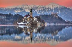 Le lac a saigné, l'église de l'acceptation de Vierge Marie, île saignée, Slovénie - coucher du soleil dans la violette Image libre de droits