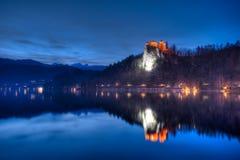 Le lac a saigné la vue sur le château la nuit en Slovénie Photographie stock
