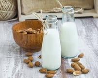 Le lait d'amande dans des bouteilles avec des écrous d'amande roulent Images stock