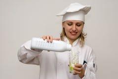 le lait en verre de beau cuisinier se renverse Photographie stock