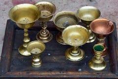 Le lampade a olio buddisti, sulle alte gambe, stanno su un vecchio vassoio di legno scuro, preparante per un servizio di sera nel Fotografia Stock Libera da Diritti