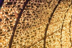 Le lampadine brillano alle luci del tunnel ed al fondo del bokeh dell'oro Fotografia Stock