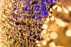 Le lampadine brillano alle luci del tunnel ed al fondo del bokeh dell'oro Fotografia Stock Libera da Diritti