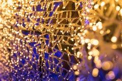 Le lampadine brillano alle luci del tunnel ed al fondo del bokeh dell'oro Fotografie Stock