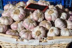 Le lampadine dell'aglio impilano in un canestro, alla luce solare, sulla vendita in un mercato fotografia stock