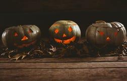 Le lanterne di Jack o con le foglie di autunno hanno sistemato sulla tavola Immagine Stock