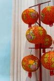Le lanterne rosse hanno decorato vicino ad una parete fotografie stock