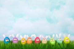 Le lapin de Pâques coloré de visages drôles eggs dans une rangée sur l'herbe Photo libre de droits