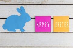 Le lapin de Pâques et les Joyeuses Pâques textotent sur des autocollants sur la table en bois blanche Image stock