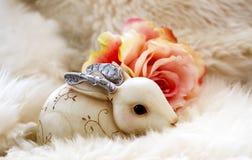 Le lapin fleuri de Noël avec les oreilles argentées en métal jetant un coup d'oeil hors de la fourrure blanche avec la pêche moll Photographie stock