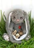 Le lapin tient des oeufs dans des ses pattes sur un fond en bois blanc Jour de Pâques Photo stock