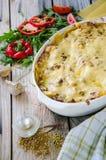 Le lasagne al forno tradizionali hanno fatto con la salsa bolognese e la salsa besciamella del manzo tritato con pepe e le erbe fotografia stock libera da diritti