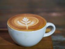 Le latte d'art est sur la soucoupe en bois Photos libres de droits