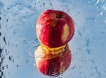 Le lavage d'une pomme rouge avec la réflexion et avec éclabousse et goutte d'eau images stock
