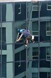 Le laveur de vitres travaille au bâtiment ayant beaucoup d'étages Photographie stock