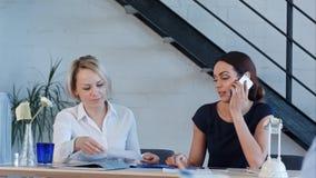 Le lavoratrici stanno lavorando nell'ufficio, avendo le telefonate e lavoro di ufficio Immagine Stock