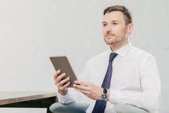 Le laywer masculin caucasien réfléchi pense à quelque chose, tient la tablette moderne, utilise la chemise blanche avec le lien n images libres de droits