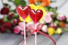 Le lecca-lecca nel cuore modellano su fondo delle rose variopinte Immagini Stock