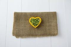 Lenticchie verdi in un cuore Fotografia Stock Libera da Diritti