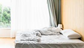Le lenzuola ed i cuscini incasinati dopo le notti dormono, la comodità e lettiera in una camera di albergo, viaggio di concetto e Fotografie Stock Libere da Diritti