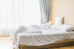 Le lenzuola ed i cuscini incasinati dopo le notti dormono, la comodità e lettiera in una camera di albergo, viaggio di concetto e Fotografia Stock