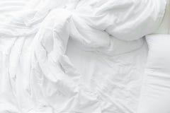 Le lenzuola ed i cuscini incasinati dopo le notti dormono, la comodità e lettiera in una camera di albergo, viaggio di concetto e Fotografie Stock