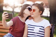 Le lesbiche delle donne godono dell'ozio in parco, posa per la fabbricazione del selfie in Smart Phone Baci abbastanza femminili  immagine stock
