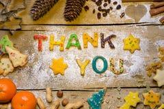 Le lettere del biscotto con la decorazione di natale sulla tavola di legno, ringraziano fotografia stock