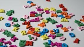 Le lettere dell'alfabeto su di legno frugano i pezzi sparsi stock footage