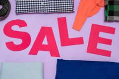 Le lettere rosa hanno tagliato dalla carta del cartone fra i vestiti Fotografie Stock Libere da Diritti