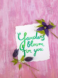 Le lettrage d'aquarelle et l'alpina violet foncé de clématite fleurit Image stock