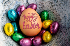 Le lettrage 2017 heureux de Pâques sur l'oeuf a garni du petit chocolat par exemple Photographie stock libre de droits