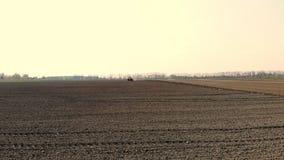 Le levé aérien, un grand tracteur monte par un champ labouré de sol noir, soulevant un nuage de la poussière derrière lui plantat banque de vidéos