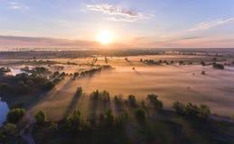 Le lever de soleil aérien avec le brouillard à l'arbre complète dans la campagne rurale Images stock